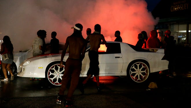 A person accelerates a car, causing the back tires to smoke, along West Florissant Avenue, Aug. 9, 2015, in Ferguson, Mo.