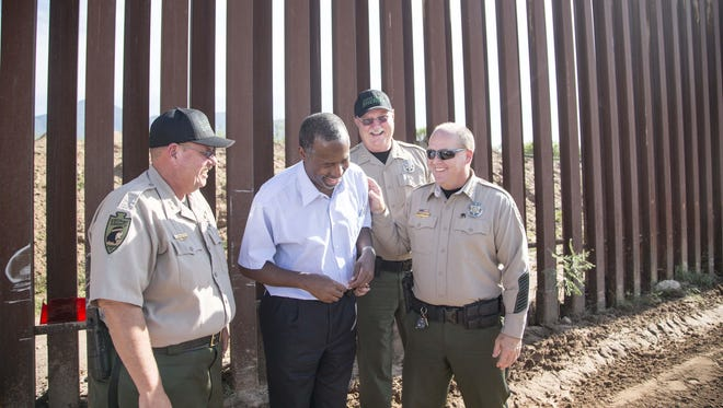 Republican presidential candidate Ben Carson shares a laugh with Cochise County Sheriff Mark Dannels (right) and deputies during a tour of the U.S.-Mexico border near Naco, Ariz.