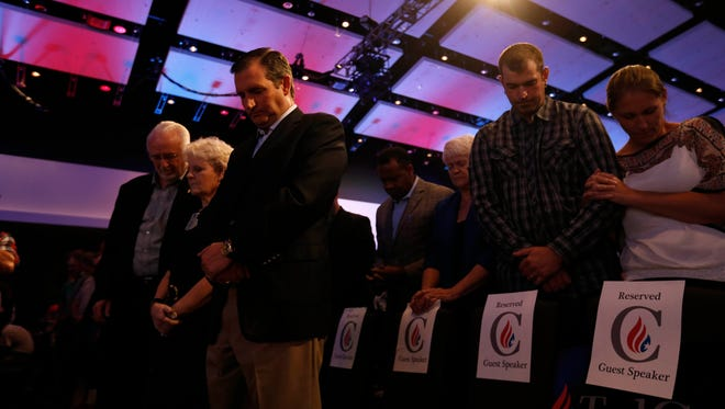 Republican Ted Cruz bows his head in prayer Friday, Aug. 21, 2015 with some of his guest speakers at the Rally for Religious Liberty in Des Moines.