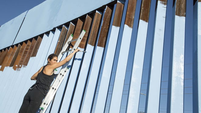 "Artist Ana Teresa Fernandez paints the border fence blue for her ""Erasing the Border"" project in Nogales, Mexico on Monday, Oct. 13, 2015."