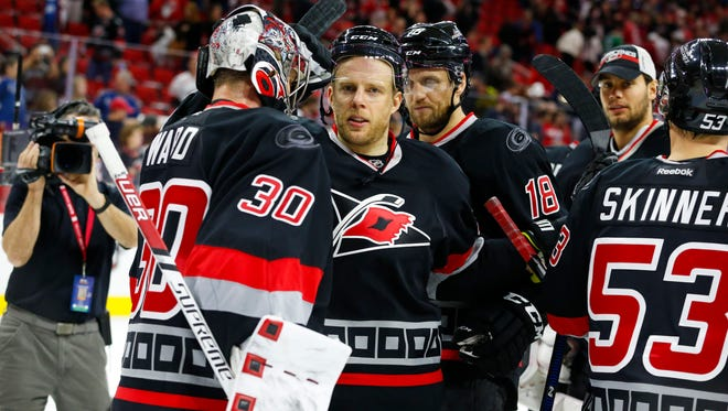 Carolina Hurricanes forward Kris Versteeg (32) congratulates teammate goalie Cam Ward (30) after the game against the Colorado Avalanche at PNC Arena.