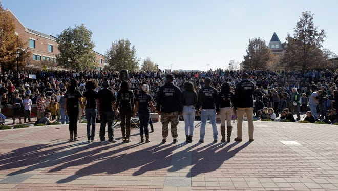 Members of black student protest group, Concerned Student 1950, hold hands  following the announcement University of Missouri System President Tim Wolfe would resign Monday, Nov. 9, 2015, at the University of Missouri in Columbia, Mo. Wolfe resigned Monday with the football team and others on campus in open revolt over his handling of racial tensions at the school.