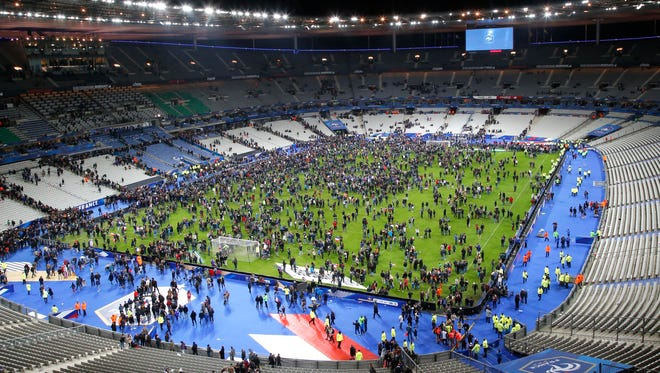 Spectators move onto the field at the Stade de France after three explosions near the stadium