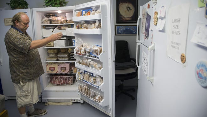 John Parrott, puts donated food by Waste Not, in a refrigerator at Shepherd's Warehouse food bank in Tempe.