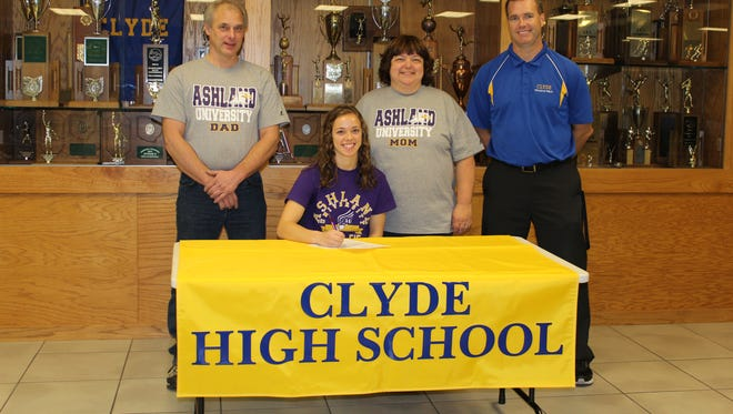 Clyde High School senior Paula Wollenslegel (sitting) signs a National Letter of Intent to run track and field at Ashland University with her parents, Mark, left, and Mary Ellen, middle, and coach Steve Baker.
