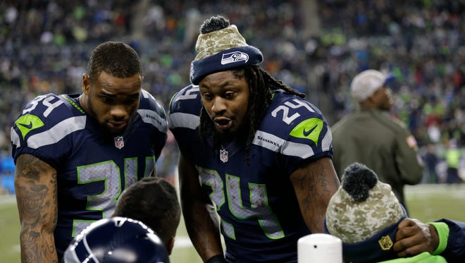 Seattle Seahawks running back Marshawn Lynch talks to teammates on the sideline in the second half of an NFL football game against the Arizona Cardinals, Sunday, Nov. 15, 2015, in Seattle.