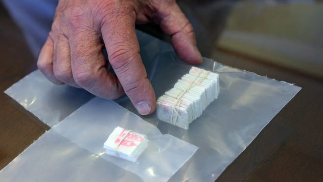 File An example of a stamped bundle and brick of heroin.
