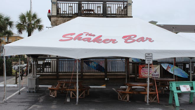 """A tent outside the Sandshaker Lounge & Package Store displays the name, """"The Shaker Bar."""""""