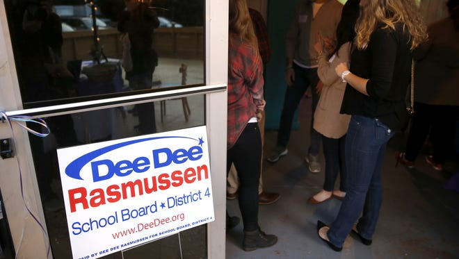 Patrons at a party for DeeDee Rasmussen sign petitions to put her name on the ballot for re-election to the Leon County School Board District 4 seat, at The Moon on Thursday.