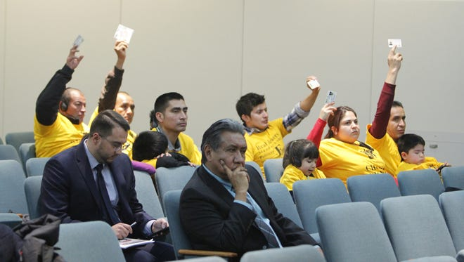 Members of the immigrant community show off their driver's licenses during a Senate Public Affair Committee meeting where they hear all of the Real ID bills on Tuesday at the State Capitol.