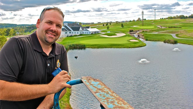 Northeastern graduate Jesse Hartman, currently the superintendent at Royal Manchester Golf Links in Mount Wolf, is seen here in this October photo with the 18th green and clubhouse in the background. Hartman was instrumental in the course rebounding from extensive damage to 90% of its putting greens.