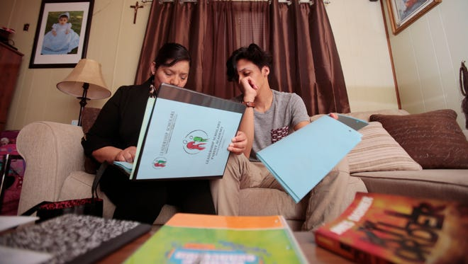 Maria Zuniga, left, and her son Jonathan Lopez, 14, right, look through her Leadership Scholars program binder, Tuesday, April 26, 2016, at her home in Sharonville, Ohio. The program is designed to help the mother of two to navigate the complex field of how to get her children to college. She has two middle-school children who now read, have access to books in the home, and are planning to attending college.