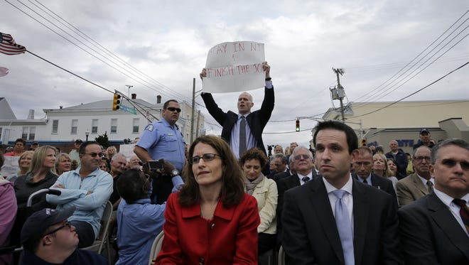 "Jim Keady holds up a sign and shouts at New Jersey Gov. Chris Christie during a event marking the second anniversary of Superstorm Sandy Wednesday, Oct. 29, 2014, in Belmar, N.J. Keady began heckling Christie about the pace of storm recovery and repeatedly interrupted the governor. After trying to brush the man off, Christie yelled back the man didn't know what he was talking about and was just showing off for the news cameras. When heckler Keady continued, Christie told him: ""Sit down and shut up."