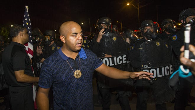 The Rev. Jarrett Maupin tries to calm tensions as police stop the Black Lives Matter marchers from continuing on Seventh Street on July 8, 2016, in Phoenix.