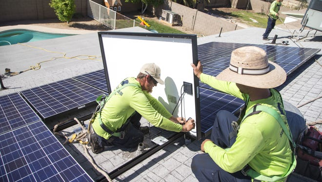 Workers install solar panels on a home in Tempe.