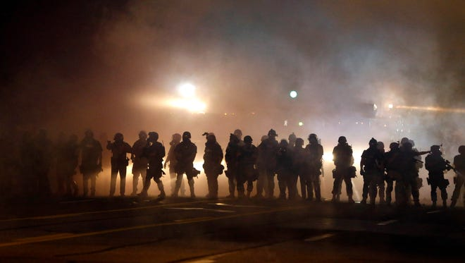 Police walk through a cloud of smoke and tear gas during protests in Ferguson, Mo.