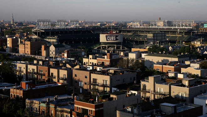 Wrigley Field sits in the center of Wrigleyville neighborhood, Friday, Oct. 7, 2016, in Chicago, before the Chicago Cubs hosts the San Francisco Giants for Game 1 of a baseball National League Division Series. Living near the workplace is one of the unique attractions of playing in a vibrant residential neighborhood like Wrigleyville. For the players and staff who take advantage, it means almost nonexistent commutes, more time with family and a chance to mingle with the surroundings in a way that might not be possible in other cities. For residents, well, you might have a Cub living next door.