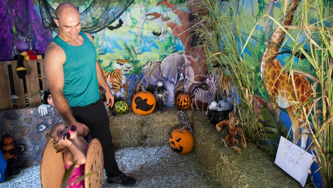 David Treglown holds his daughter Harper's, 2, hand as she looks up at the bats in the haunted tunnel during the Boo at the Zoo event at Naples Zoo on Friday, Oct. 21, 2016. For 3 days, children in costume will receive free admission and get to enjoy a trick or treat trail, costume contests and games at Boo Town.
