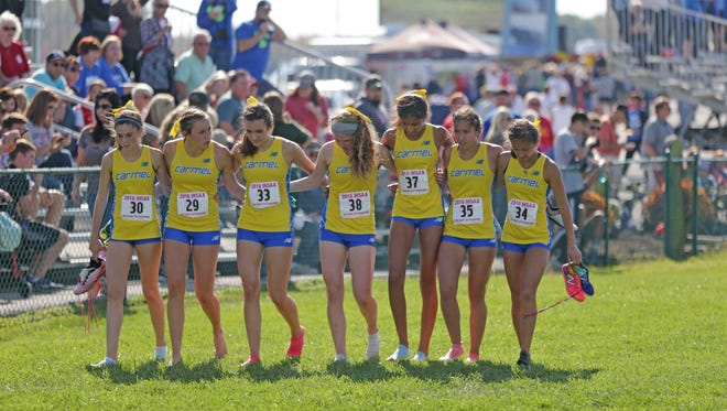 The Carmel Girls Cross Country Team links arms as they walk together after the race, during the IHSAA cross-country state finals, held in Terre Haute IN, at LaVern Gibson Championship Cross Country Course and Wabash Valley Sports Center, Saturday october 29th, 2016.
