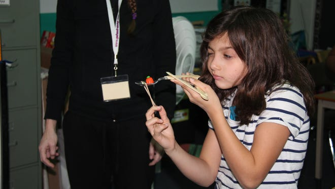 A student at Roosevelt Elementary School participates in a Spook STEM activity on Halloween.