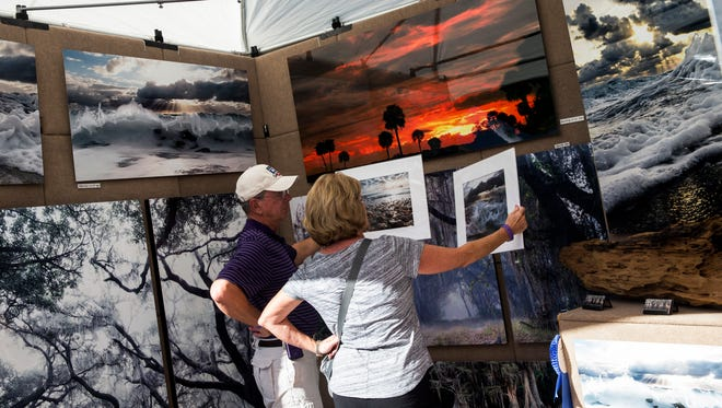 A couple compares two photos before making a purchase at the 18th bi-annual HotWorks.org Estero Fine Art Show at the Miromar Design Center on Sunday, Nov. 20, 2016. As one of the top 100 art fairs in America, the event showcases original and personally handmade art from 175 professional artists.
