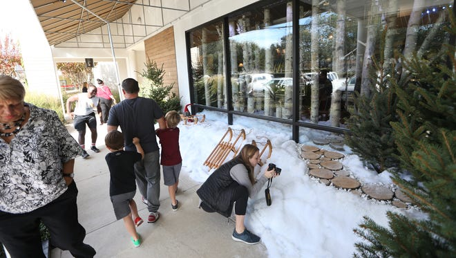 People tour through the outdoor portion of the holiday themed window display at Hearth & Soul, which continues on into the interior of the store. The display was unveiled on Wednesday and will remain at the store through the holiday season.
