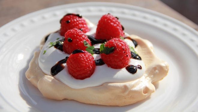 This Nov. 18, 2016, photo shows tangy raspberry (reduced sugar) pavlova with a balsamic glaze. For the uninitiated, a pavlova (named after the famed ballerina's fluffy tutu) is essentially a meringue shell baked at low heat until the outside is barely golden crisp, but the inside remains soft and billowy, like a creamy marshmallow.