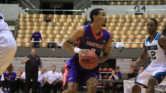 Evansville sophomore Ryan Taylor turns to look for his shot in front of UNC Wilmington sophomore C.J. Bryce during their game Saturday at the Nashville Municipal Auditorium.