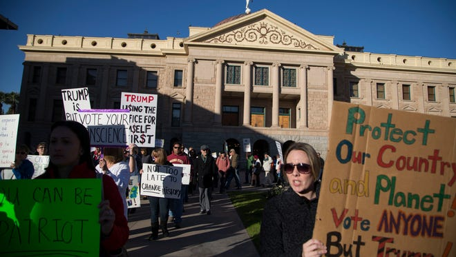 Protesters in front of the Arizona State Capitol hold signs calling for Arizona electors to not cast votes for President-Elect Donald Trump on Dec. 19, 2016 in Phoenix.