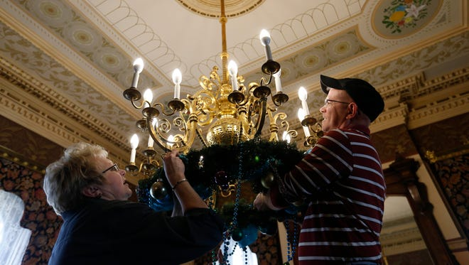 Fran Newsom of Waterloo (left) and Laurel Hollopeter hang a wreath on a chandelier Thursday, Nov. 17, 2016, as dozens of volunteers help get Terrace Hill in Des Moines ready for the holidays.