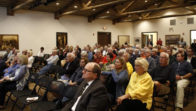 Marco Island residents listen to a presentation about the revised Veterans Community Park hotel project on Tuesday, Jan. 10 in Rose History Auditorium. In front sits Patrick Neale, one of the developer's representatives.
