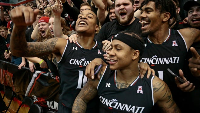 Cincinnati Bearcats guard Troy Caupain (10) and his teammates celebrate in the student section after the game.