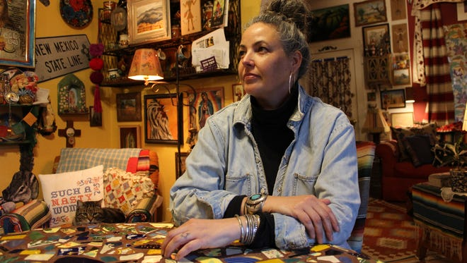 """Photographer Mattie Kannard sits at table at her home in Mesilla on Friday, Feb. 17, 2017. Kannard, who is self taught in photography, started taking photographs of painted over graffiti, or """"buff,"""" in 2009."""