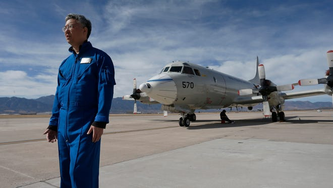 In this Feb. 17, 2017, photo, Ed Kim, a NASA researcher and lead scientist for a NASA-led experiment called SnowEx, stands near a Navy P-3 Orion aircraft used for SnowEx, at Peterson Air Force Base in Colorado Springs, Colo. Airplanes are scanning the Colorado high country with an array of sensors as scientists search for better ways to measure how much water is locked up in the world's mountain snows.
