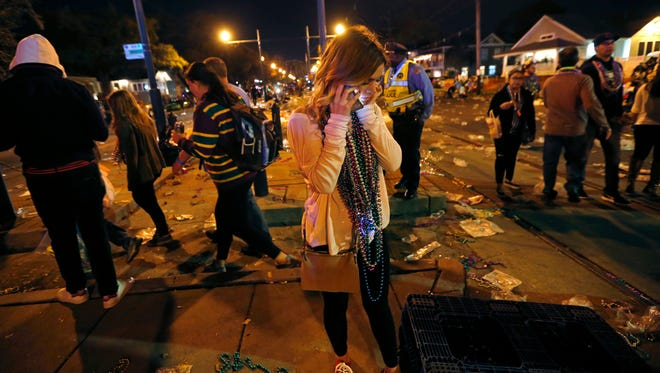 A woman talks on a phone at the scene of where a truck slammed into a crowd and other vehicles, causing multiple injuries, during the Krewe of Endymion parade in in the Mid-City section of New Orleans, Saturday, Feb. 25, 2017. Police Chief Michael Harrison says one person in custody and that he is being investigated for driving while intoxicated.
