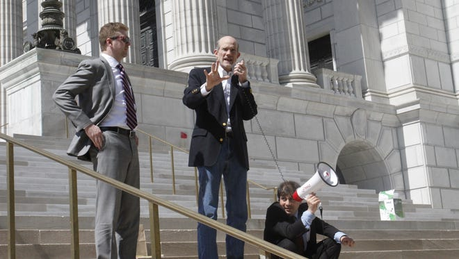 John Hickey, center, director of the Sierra Club's Missouri chapter, talks to a crowd outside the Capitol on Wednesday, April 12, 2017. Hickey's words were also directed at Logan Spena, left, deputy policy director for Gov. Eric Greitens, and were amplified with the help of Sierra Club organizer Michael Berg, right.
