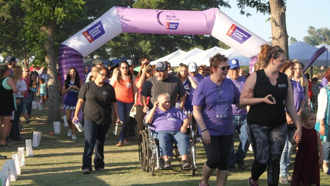 Cancer survivors and their families participate in the walk for Relay for Life in Carlsbad on Friday. About 200 survivors participated in the event.