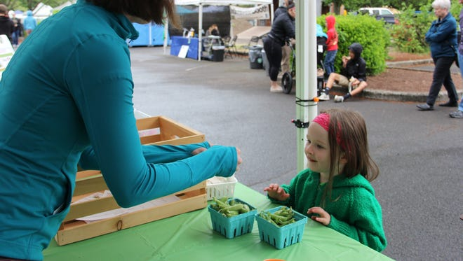 Marin Krumenauer, 3, learns how to open a snap pea pod at POP Club, a produce education program at the Salem Saturday Market. The hands-on event runs 10 a.m. to 2 p.m. each Saturday through August.