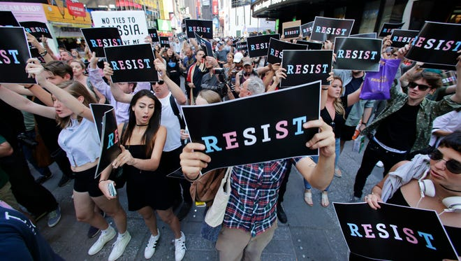 """Protestors gather in Times Square, Wednesday, July 26, 2017, in New York. President Donald Trump declared a ban Wednesday on transgender troops serving anywhere in the U.S. military, catching the Pentagon flat-footed and unable to explain what it called Trump's """"guidance."""""""