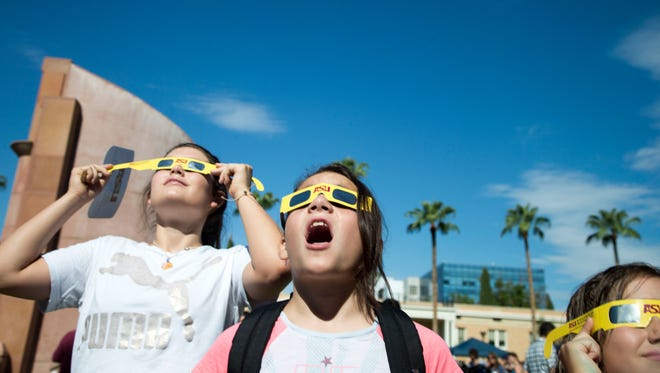 Visitors to ASU's Tempe campus watch the solar eclipse on Aug. 21, 2017. Many parents brought their children to see the rare solar eclipse.