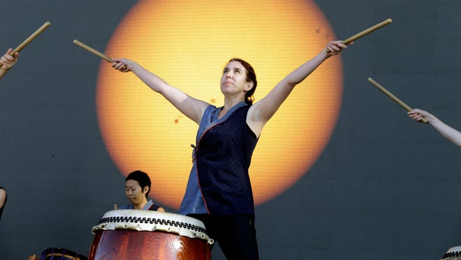Portland Taiko drummer Karen Tingey performs in front of a live video shot of the sun to introduce the solar eclipse from Salem, Ore., Monday, Aug. 21, 2017.
