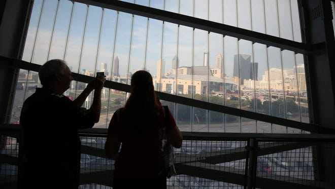 Fans take a photograph of the Atlanta skyline shown through a large window before the Atlanta Falcons game against the Arizona Cardinals at Mercedes-Benz Stadium.