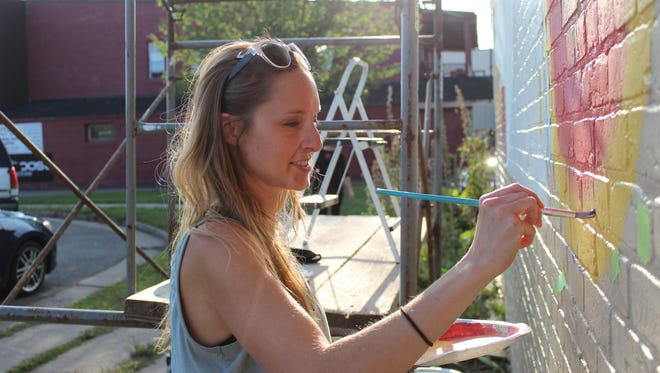 Jessica Kopecky carefully works on the outline of a flower in the summer portion of her mural.