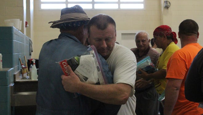 Pastor Dick DeBusk hugs a Grant Parish Detention Center inmate after he received a care package.