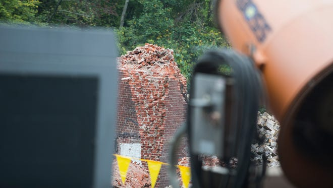 Rubble lays where a 230-foot smokestack was imploded on the grounds of the former Bancroft Mills Sunday morning to make way for a redevelopment project.