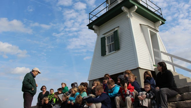 Rich Norgard, left, discusses the history of the Port Clinton Lighthouse with students from Immaculate Conception School's third, fourth and fifth grades.