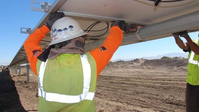 A construction worker helps build the 20-megawatt Apache Solar Project outside of Benson, Arizona.