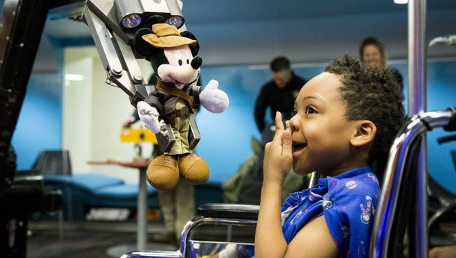 Justice Dean, 6, smiles at the police robot bringing him a Christmas gift at the Phoenix Children's Hospital. Phoenix Police officers were making a special appearance to visit with those children who can't be home for the holidays.