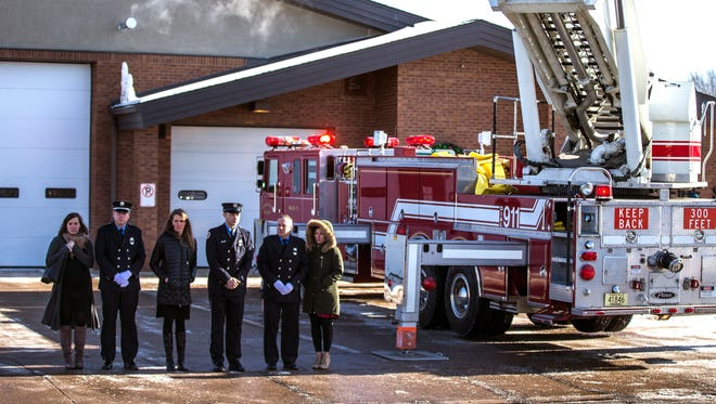 People watch the funeral procession for Wisconsin Rapids Fire Department Firefighter Jim Easton as it passes the fire department in Wisconsin Rapids, Wis., Friday, January 5, 2018.