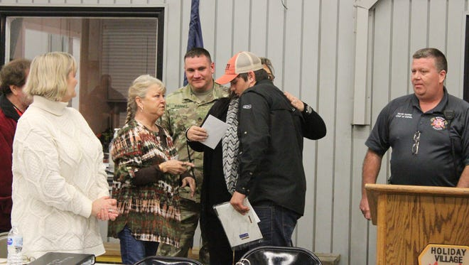 Daniel Carr (right) gets a hug from the family whose members he helped save from a January fire. He and a friend, Kolton Mitchell, were honored for their actions by the Holiday Village Fire Department.